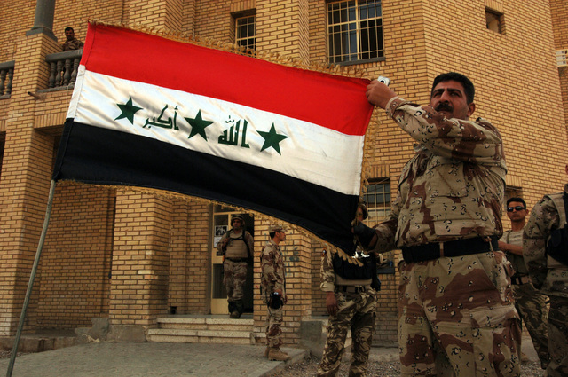 An Iraqi soldier holds Iraq's flag high in sign of patriotism, after providing security for the Iraqi permanent parliamentary elections on Dec. 15, 2005.  These elections will set the path to a future democracy in Iraq for the next four years.(U.S. Army photo by SPC. Teddy Wade) (Released)