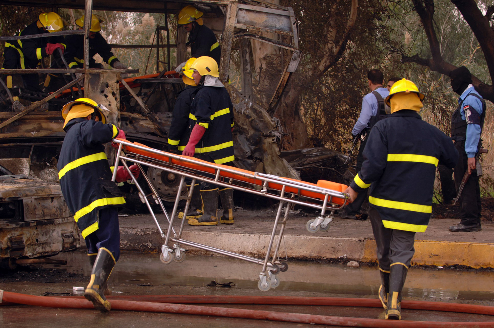 Ba'Qubah City Fire fighters bring stretchers onto the scene of en exploded bus that was to escort 18 Iraqi policemen to the Police Academy in Solaymanya, Iraq on Jan. 2, 2006. (U.S. Army photo by SPECIALIST Danielle Howard) (Released)
