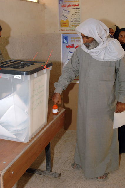 Iraqi man dips his finger into the ink to mark his ballet for the elections, on Dec. 15, 2005, downtown Baghdad.  The elections are the first free elections ever conducted for the perment parlimentary government in Iraq.   (U.S. Army photo by PFC. William Servinski II) (Released)