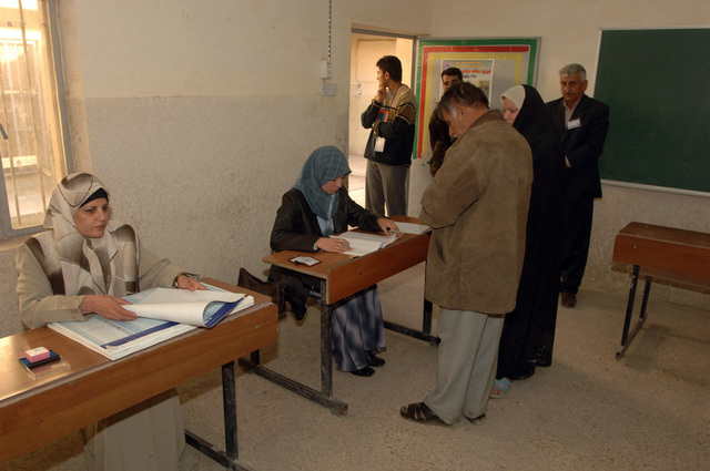 Iraqi man recieves his ballet to vote for the elections, on Dec. 15, 2005, downtown Baghdad.  The elections are the first free elections ever conducted for the perment parlimentary government in Iraq.   (U.S. Army photo by PFC. William Servinski II) (Released)