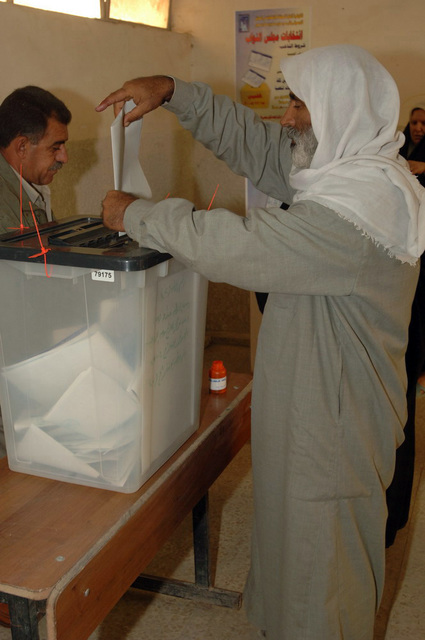 Iraqi man submits his vote into the voting box, on Dec. 15, 2005, downtown Baghdad.   The elections are the first free elections ever conducted for the perment parlimentary government in Iraq.   (Released)   (U.S. Army photo by PFC. William Servinski II)