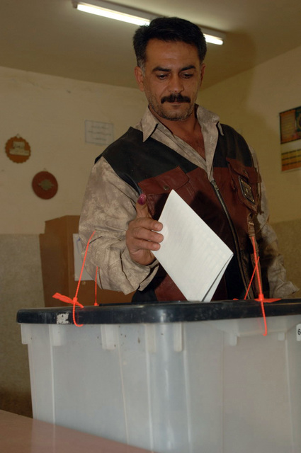 Iraqi man submits his vote into the voting box, on Dec. 15, 2005, downtown Baghdad.  The elections are the first free elections ever conducted for the perment parlimentary government in Iraq.   (U.S. Army photo by PFC. William Servinski II) (Released)