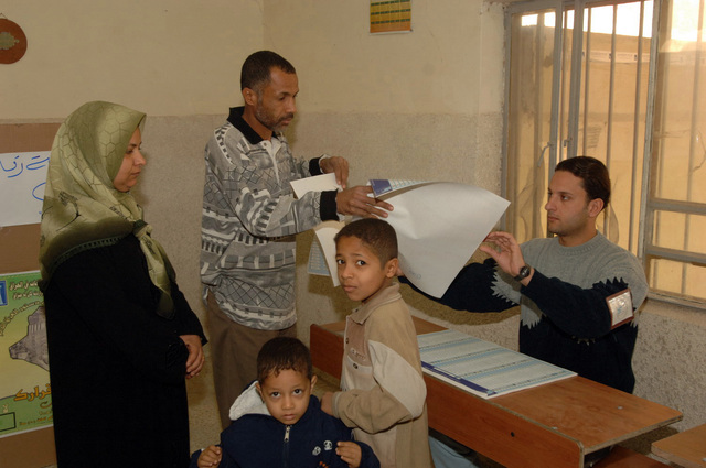 Iraqi man with his family recieves his ballet to vote for the elections, on Dec. 15, 2005, downtown Baghdad.  The elections are the first free elections ever conducted for the perment parlimentary government in Iraq.   (U.S. Army photo by PFC. William Servinski II) (Released)