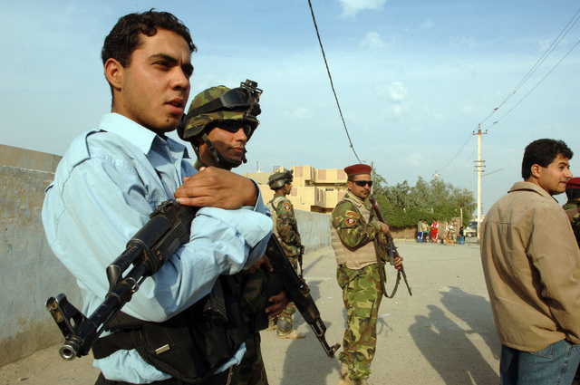 Iraqi Police men provide security outside a polling site in Sadr City, Iraq during the Iraqi permanent parliamentary elections on Dec. 15, 2005.  These elections will set the path to a future democracy in Iraq for the next four years.(U.S. Army photo by SPC. Teddy Wade) (Released)