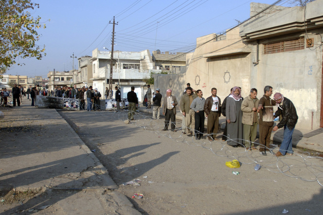 Iraqi voters go through a security check before being allowed to vote on the morning of their elections.  Mosul in Support of Operation Iraqi Freedom. (U.S. Army photo by STAFF SGT. James H. Christopher III) (Released)
