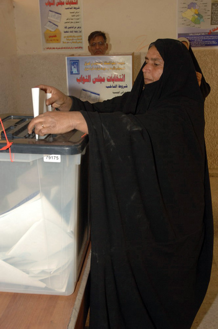 Iraqi woman submits her vote into the voting box, on Dec. 15, 2005, downtown Baghdad.   The elections are the first free elections ever conducted for the perment parlimentary government in Iraq.   (Released)   (U.S. Army photo by PFC. William Servinski II)