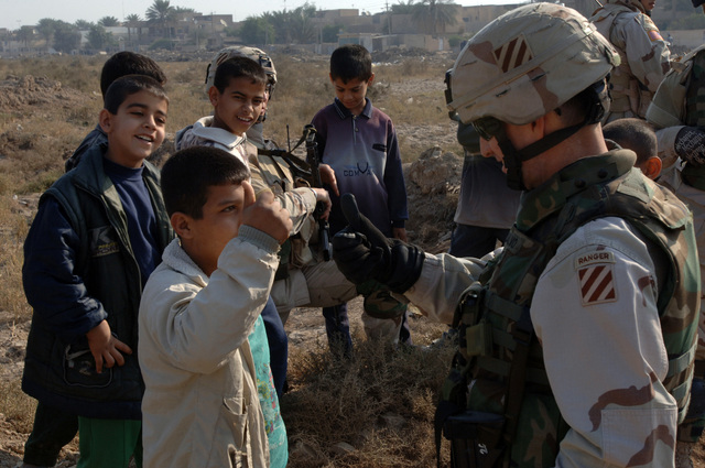 U.S. Army COL. Joseph Disalvo, the Commander of the 2nd Brigade Combat Team, 3rd Infantry Division play with Iraqi children while providing security outside a polling site in the Zafaraniyah District Baghdad, Iraq during the Iraqi permanent parliamentary elections on Dec. 15, 2005.  These elections will set the path to a future democracy in Iraq for the next four years. (U.S. Army photo by SPC. Teddy Wade) (Released)