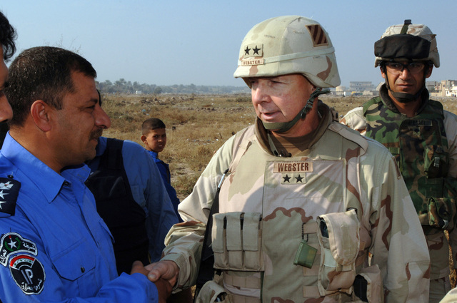 U.S. Army MAJ. GEN. William Webster, the 3rd Infantry Division Commander shake hands with an Iraqi police officer during the Iraqi permanent parliamentary elections in Zafaraniyah, Iraq on Dec. 15, 2005. These elections will set the path to a future democracy in Iraq for the next four years. (U.S. Army photo by SPC. Teddy Wade) (Released)