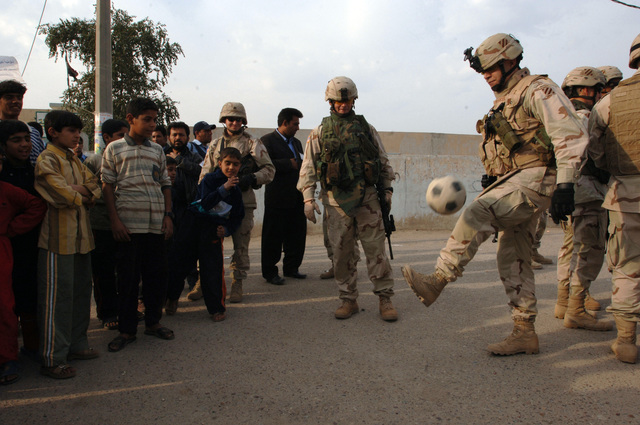 U.S. Army Soldiers from the 2nd Brigade Combat Team, 3rd Infantry Division play soccer with Iraqi children during a short break outside a polling site in Sadr City, Baghdad on Dec. 15, 2005. The Soldiers were providing security for the Iraqi permanent parliamentary government elections as well as guarding VIP members of the military. (U.S. Army photo by SPC. Teddy Wade) (Released)