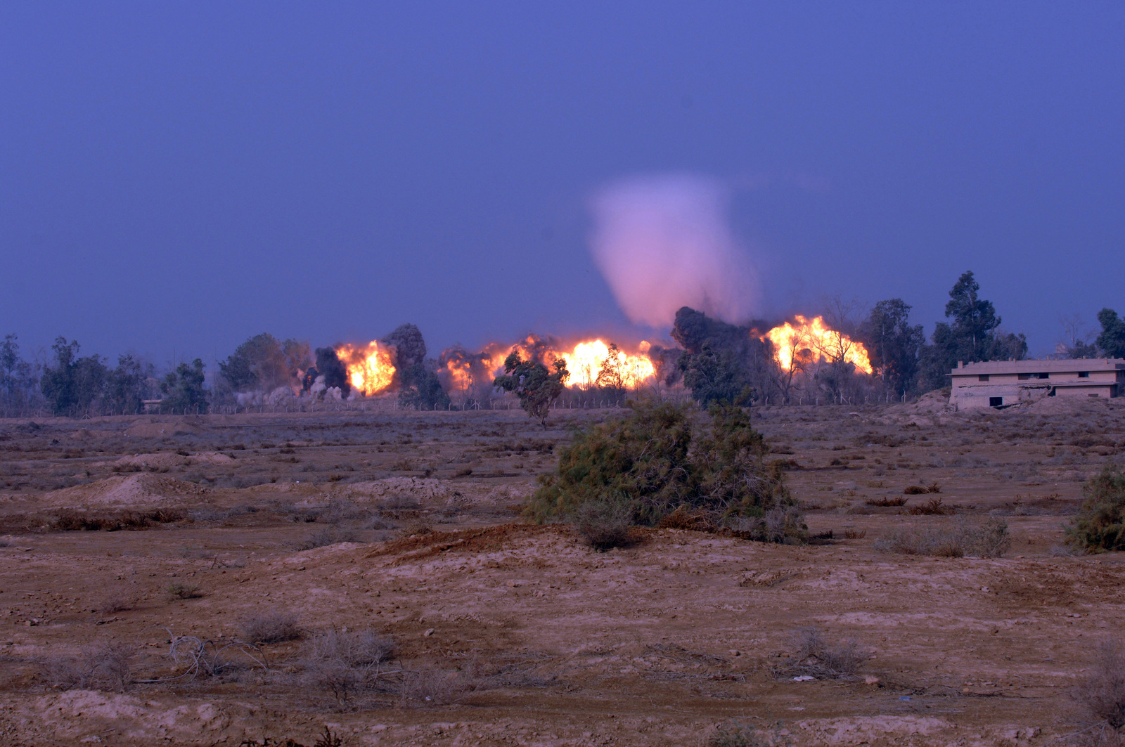 A fireball and shockwave made from the joint disposal of seven 1000 pound bombs left over from Saddam Hussein's regime. The disposal was carried out by the 710th Ordnance Company (EOD) near Taji, Iraq Dec. 16, 2005.(U.S. Army PHOTO by: PVT. Ronald Gaete) (Released)