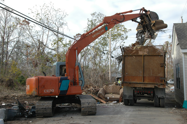 [Hurricane Katrina] Pass Christian, Miss., December 21, 2005 -- Debris removal in Pass Christian continues as this truck is being filled by a worker operating a hydraulic excavator.  Pass Christian is devastated by Hurricane Katrina.  Mark Wolfe/FEMA