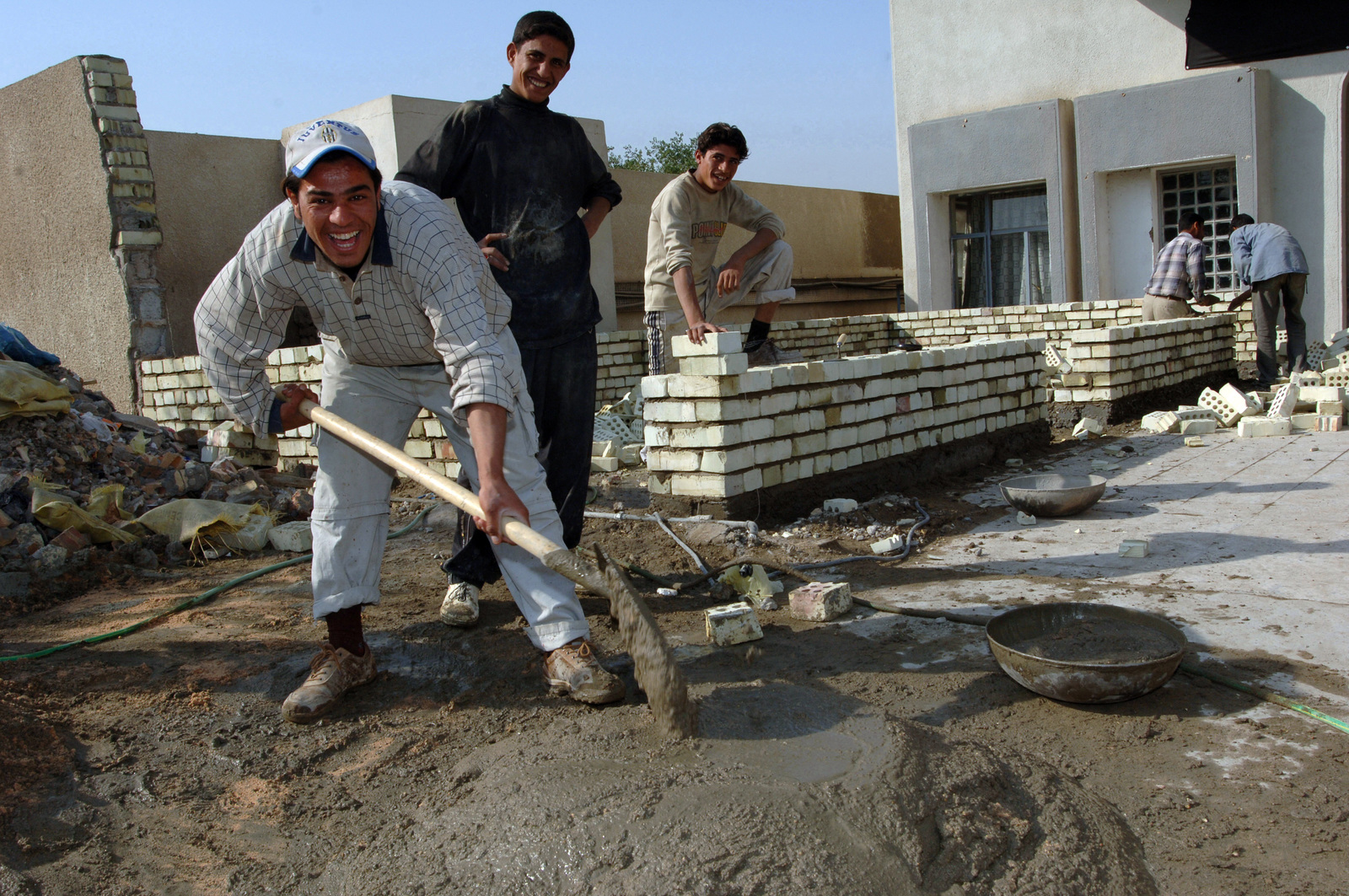 Iraqi workers mix cement to build walls outside the Civil