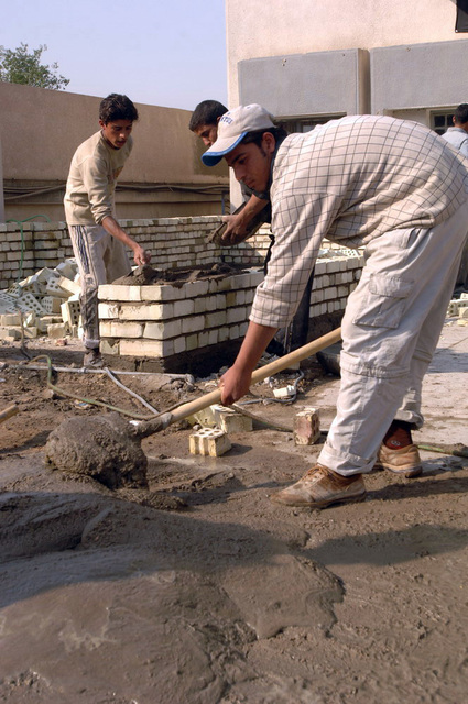 Iraqi workers mix cement to build walls outside the Civil Defence Headquarters, Dec. 24, 2005, Sadr City, Baghdad, Iraq.   The Civil Defence headquarters is where they station their fire department and EOD teams. (U.S. Army photo by PFC. William Servinski II) (Released)