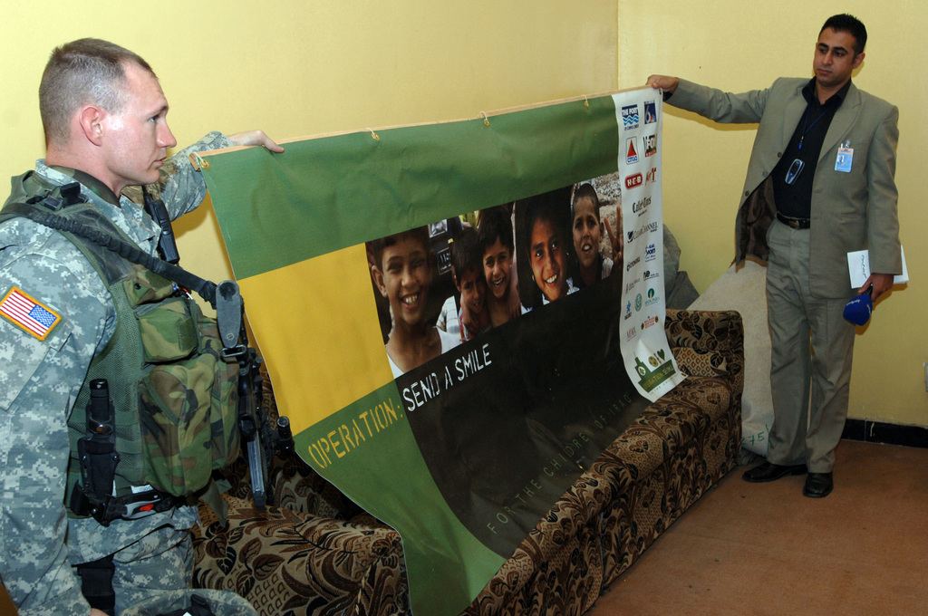 """U.S. Army STAFF SGT. Darren Logsdon, left, from Bravo Company, 448th Civil Affairs Battalion and an Iraqi youth sports parliament member holds up an Operation""""Send A Smile""""banner during a meeting in Sadr City, Baghdad, Iraq, Dec. 24, 2005. Citizens of Corpus Christi, Texas and different privates organizations from the United States sponsored Operation""""Send A Smile"""". (U.S. Army photo by SPC. Teddy Wade) (Released)"""
