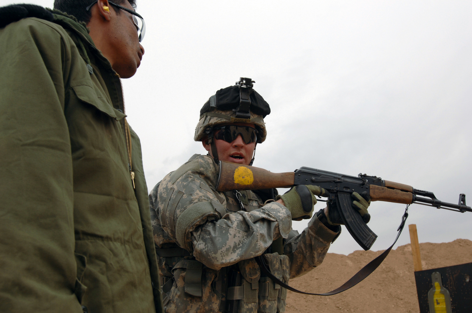 U.S. Army SPECIALIST Toby Cagle, from Headquarters Headquarters Company, 1-327th Infantry Regiment, 101st Airborne Division, Fort Campbell, KY, shows an Iraqi Army soldiers the proper way to hold the weapon during Close Quarters Combat training, on Forward Operating Base McHenry, Iraq, on Jan. 2, 2006. (U.S. Army photo by SPC Timothy Kingston) (Released)