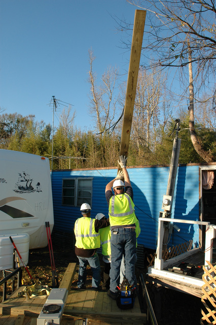 [Hurricane Katrina] Pearl River County, Miss., January 3, 2006 -- Bechtel employees install a power pole and electric meter to bring electricity to a FEMA provided travel trailer.  All utilities must be turned on before travel trailers can be occupied.  Mark Wolfe/FEMA