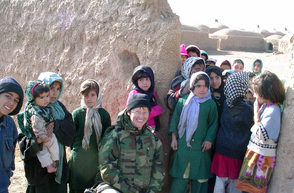 US Navy (USN) Commander (CDR) Kim Evans stops to pose for a photo with children from the Ghoryan District. Evans is the first female Commanding Officer (CO) of a Provincial Reconstruction Team in Afghanistan (AFG), in support of Operation ENDURING FREEDOM