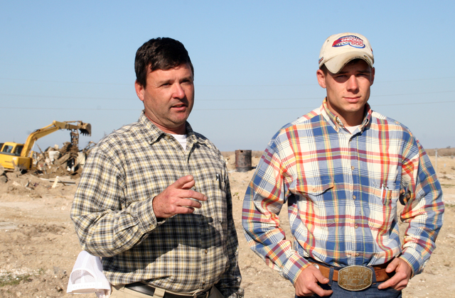 """[Hurricane Rita] Holly Beach, LA, January 11, 2006 - Eric Monceaux (L) points to where his Holly Beach properties once stood before Hurricane Rita destroyed the entire area.  With equipment donated by Jason Young (R) and the help of FEMA, the community once referred to as the """"Cajun Riviera"""" begins its clean-up with intent to rebuild.  Robert Kaufmann/FEMA"""