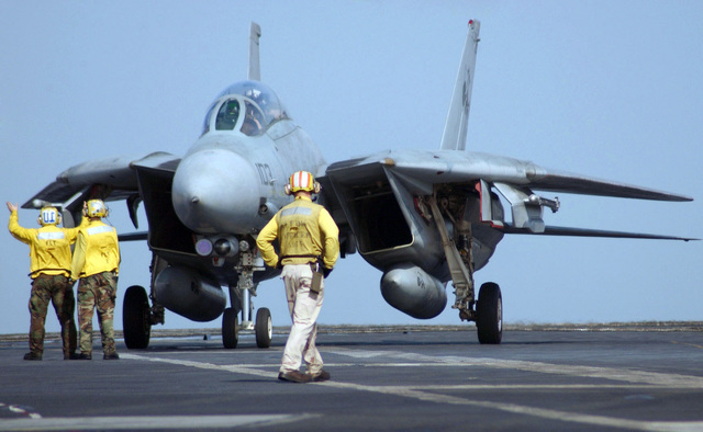 US Navy (USN) aircraft handlers direct a USN F-14D Tomcat fighter, Fighter Squadron 31 (VF-31), Tomcatters, Naval Air Station (NAS) Oceana, Virginia (VA), into launch position on the flight deck aboard the USN Nimitz Class Aircraft Carrier USS THEODORE ROOSEVELT (CVN 71). The ROOSEVELT and embarked Carrier Air Wing 8 (CVW-8) are currently underway on a regularly scheduled deployment conducting maritime security operations (MSO) on the Persian Gulf