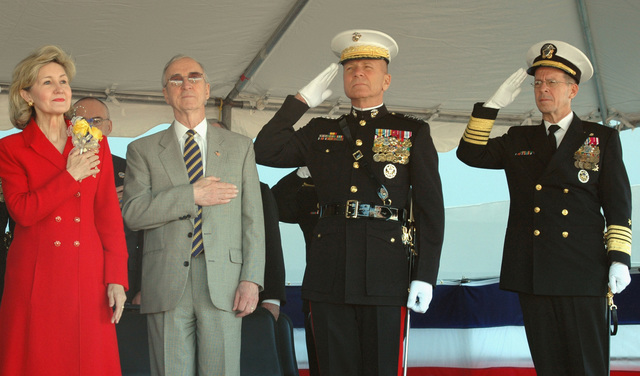 Members of the Official Party stand to render honors, during the Commissioning Ceremony for the US Navy (USN) Amphibious Transport Dock, USS SAN ANTONIO (LPD 17) (not shown), held pier side at Naval Station Ingleside, Texas (TX). Pictured foreground left-to-right: the Ships sponsor, US Senator, The Honorable Kay Bailey Hutchison (R-TX); US Deputy Secretary of Defense, The Honorable Gordon R. England; US Marine Corps (USMC) General (GEN) Michael W. Hagee, Commandant of the Marine Corps (CMC); and USN Admiral (ADM) Michael G. Mullen, CHIEF of Naval Operations (CNO)