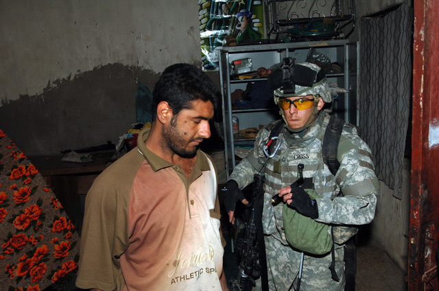 PFC Kyle Cross from B Battery, 4-320th Field Artillery Battalion, 101st Division escort an Iraqi civilian while Iraqi police officers perform a search inside a house during operation blackfoot in the Zafaraniyah District, Baghdad on January 16, 2005. The Iraqi Police and US Soldiers were looking for Weapons caches suspected to be hidden in that area. The 101st Division is currently deployed in Iraq supporting Operation Iraqi Freedom.(U.S. Army photo by SPECIALIST Teddy Wade) (Released)