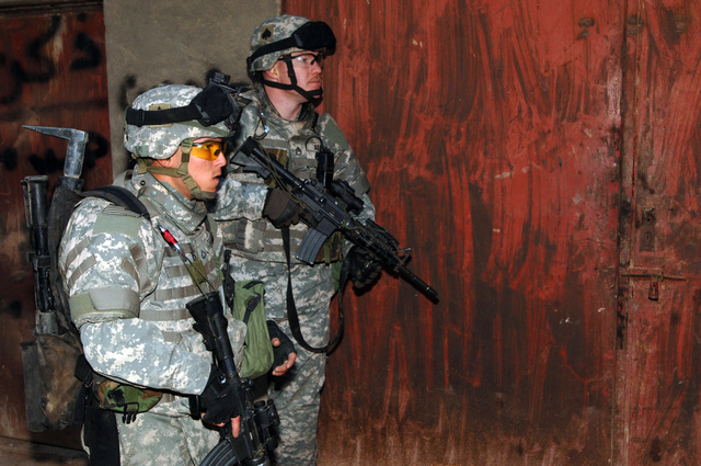 STAFF SGT. Ryan Beagle and PFC Kyle Cross from B Battery, 4-320th Field Artillery Battalion, 101st Division provide security outside a warehouse during operation blackfoot in the Zafaraniyah District, Baghdad on January 16, 2005. The Iraqi Police and US Soldiers were looking for Weapons caches suspected to be hidden in that area. The 101st Division is currently deployed in Iraq supporting Operation Iraqi Freedom.(U.S. Army photo by SPECIALIST Teddy Wade) (Released)