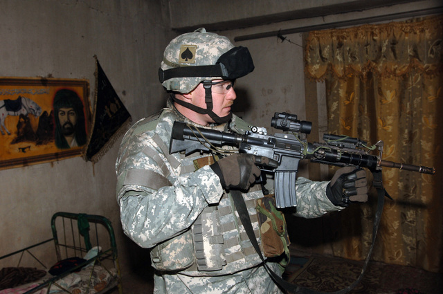 STAFF SGT. Ryan Beagle from B Battery, 4-320th Field Artillery Battalion, 101st Division provide rear security inside a house while Iraqi police officers perform a search during operation blackfoot in the Zafaraniyah District, Baghdad on January 16, 2005. The Iraqi Police and US Soldiers were looking for Weapons caches suspected to be hidden in that area. The 101st Division is currently deployed in Iraq supporting Operation Iraqi Freedom.(U.S. Army photo by SPECIALIST Teddy Wade) (Released)