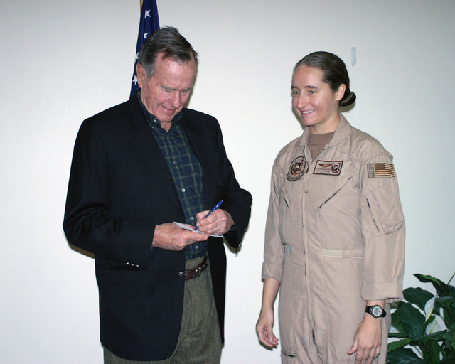 Former US President George H. W. Bush (left) sings an autograph for US Navy (USN) Aviation Machinist's Mate First Class (AD1) Cindy Baker, during Mr. Bushs recent visit at Al Udeid Air Base (AB), Qatar. AD1 Baker, assigned to Patrol Squadron Four Seven (VP-47) received the honor after being named the USN SENIOR Sailor of the Year