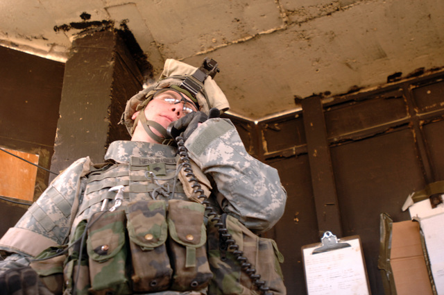 SPECIALIST Matthew Henninger of Bravo Company, Task Force 1/87, 10th Mountain Division responds to a radio call at his post on FOB Abu Ghiraib on January 18th, 2006. (US Army photo by PFC Nathaniel Lawrence)(RELEASED)