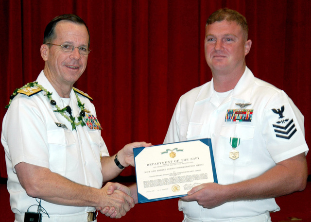 US Navy (USN) Admiral (ADM) Michael G. Mullen (left), CHIEF of Naval Operations (CNO), presents a Navy and Marine Corps Commendation Medal to USN Aviation Structural Mechanic First Class (AM1) Larry D. Cummins, Commander, Patrol and Reconnaissance Wing 2 (VPU-2), for heroic achievement in the rescuing of a 15-year-old girl. USN AM1 Cummins entered the water of the Ala Wai Canal in Honolulu, Hawaii (HI), in search of a car that went off a pier. He gained access to the vehicle, freed the unconscious occupant and returned her to shore where she received CPR and eventually made a full recovery