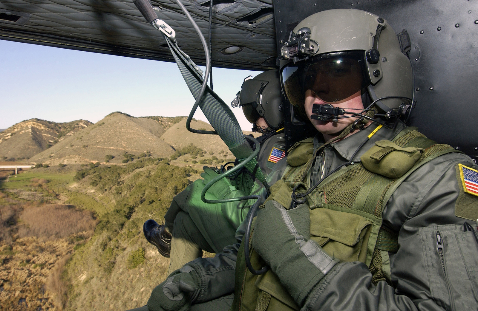 US Air Force (USAF) AIRMAN First Class (A1C) Erik McCarick, Flight Engineer, 76th Helicopter Squadron, Vandenberg Air Force Base (AFB), California (CA), scans the San Luis Obispo county scenery from his seat on a USAF UH-1N Helicopter