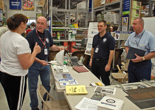 [Hurricane Rita] Sulphur, LA, 1-26-06 -- Ellie Newby talks with FEMA mitigation Specialists Braden Allen and John Ormsby and NFIP Specialist Tom McDermott about wind proofing hardware repairs at this mitigation display at Lowe's Building supplies.  FEMA puts these Mitigation displays in public places to give people who need to build or rebuild choices in making a better building that will resist damage better.  MARVIN NAUMAN/FEMA photo