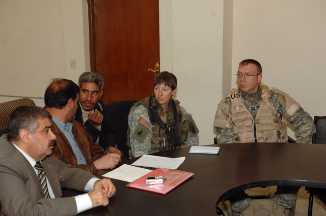 MAJ Debra Yarbrough and CPT. David MCcaughrin from the 448th Civil Affairs Battalion talk with Iraqi civilians at the neighborhood counsel hall in New Baghdad, Iraq on January 26, 2006. They are meeting to provide help to the surviving family members of a Vehicle borne improvised explosive devices incident.(U.S. Army photo by SPECIALIST Teddy Wade) (Released)