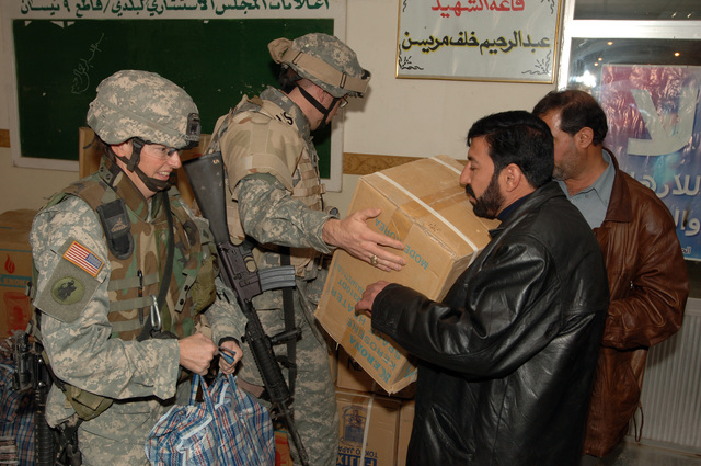 MAJ Debra Yarbrough and CPT. David MCcaughrin from the 448th Civil Affairs Battalion give away kerosine heaters and clothing bags to Iraqi civilians at the neighborhood counsel hall in New Baghdad, Iraq on January 26, 2006. The Humanitarian assistance mission was in benefit of the surviving family members of a Vehicle borne improvised explosive devices incident.(U.S. Army photo by SPECIALIST Teddy Wade) (Released)