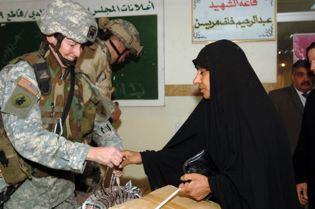 MAJ Debra Yarbrough from the 448th Civil Affairs Battalion gives a clothing bag to an Iraqi woman at the neighborhood counsel hall in New Baghdad, Iraq on January 26, 2006. The Humanitarian assistance mission was in benefit of the surviving family members of a Vehicle borne improvised explosive devices incident.(U.S. Army photo by SPECIALIST Teddy Wade) (Released)