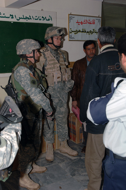 Mjr. Debra Yarbrough and CPT. David McCaughrin from Bravo Co. Civil Affairs, 448 Battalion, and Iraqi Councilmen discuss the heaters, shoes, and clothing givin out during a Humanitarian Assistance drop at the local council hall in Baghdad, Iraq, on January 26, 2006.  The supplies were given to the families of children killed from IED explosions.  The 101st is currently deployed to Iraq in support of Operation Iraqi Freedom.  (Released)    (US Army photo by Private First Class William Servinski II)