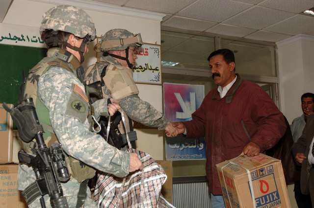 Mjr. Debra Yarbrough and CPT. David McCaughrin from Bravo Co. Civil Affairs, 448 Battalion, and Iraqi Councilmen give out heaters, shoes, and clothing during a Humanitarian Assistance drop at the local council hall in Baghdad, Iraq, on January 26, 2006.  The supplies were given to the families of children killed from IED explosions.  The 101st is currently deployed to Iraq in support of Operation Iraqi Freedom.  (Released)    (US Army photo by Private First Class William Servinski II)