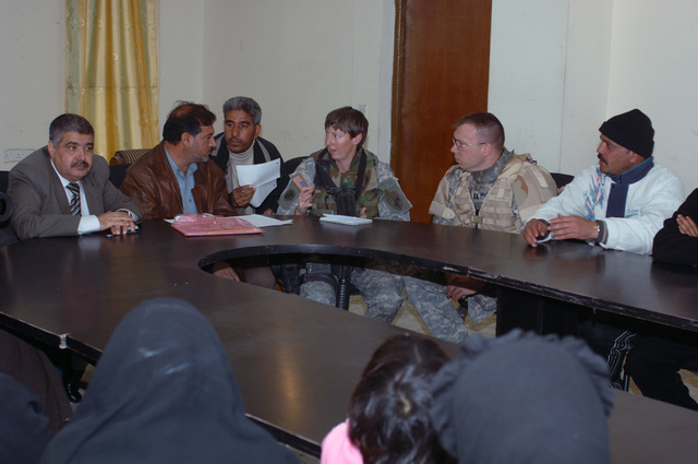 Mjr. Debra Yarbrough from Bravo Co. Civil Affairs, 448 Battalion, and Iraqi Councilmen hold a meeting discussing a trailer full of heaters, shoes, and clothing for a Humanitarian Assistance drop at the local council hall in Baghdad, Iraq, on January 26, 2006.  The supplies were given to the families of children killed from IED explosions.  The 101st is currently deployed to Iraq in support of Operation Iraqi Freedom.  (Released)    (US Army photo by Private First Class William Servinski II)