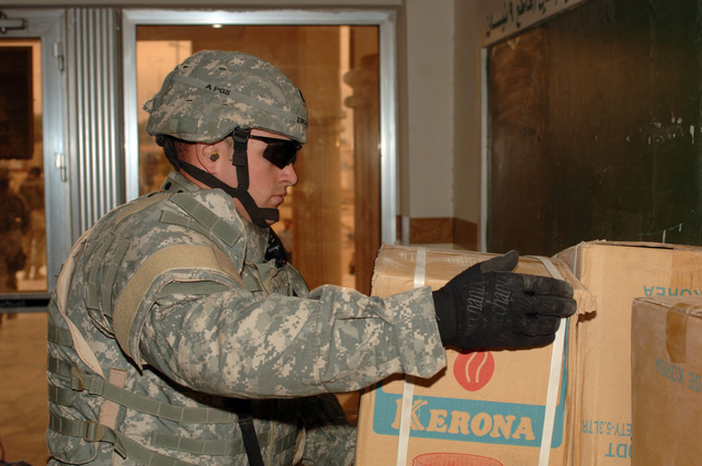 Soldiers from Bravo Co. Civil Affairs, 448 Battalion, and Iraqi Councelmen unload a trailer full of heaters, shoes, and clothing for a Humanitarian Assistance drop at the local council hall in Baghdad, Iraq, on January 26, 2006.  The supplies were given to the families of children killed from IED explosions.  The 101st is currently deployed to Iraq in support of Operation Iraqi Freedom.  (Released)    (US Army photo by Private First Class William Servinski II)