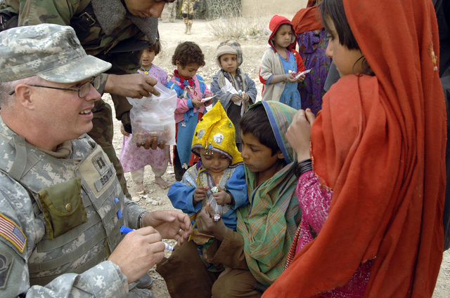 U.S. Army CAPT. Michael Benton marks the hand of an Afghan child after getting a de-wormer dose during a village medical outreach in Maywand District, Afghanistan, Jan. 27, 2006. (U.S. Army photo by SPC. Leslie Angulo) (Released)