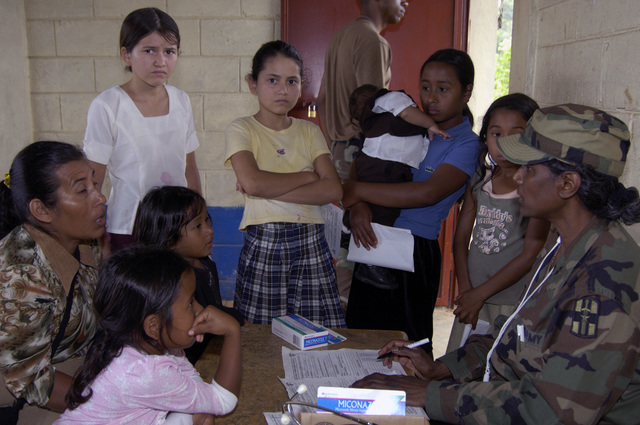 US Army CPT Clara Moses, a nurse with the 94th Combat Support Hospital, Seagoville, Texas, right, reviews the medications of a Guatemalan family during a Medical Readiness Training Exercise (MEDRETE) in Poptun, Guatemala on 27 January 2006. (US Army PHOTO by Kaye Richey) (Released)