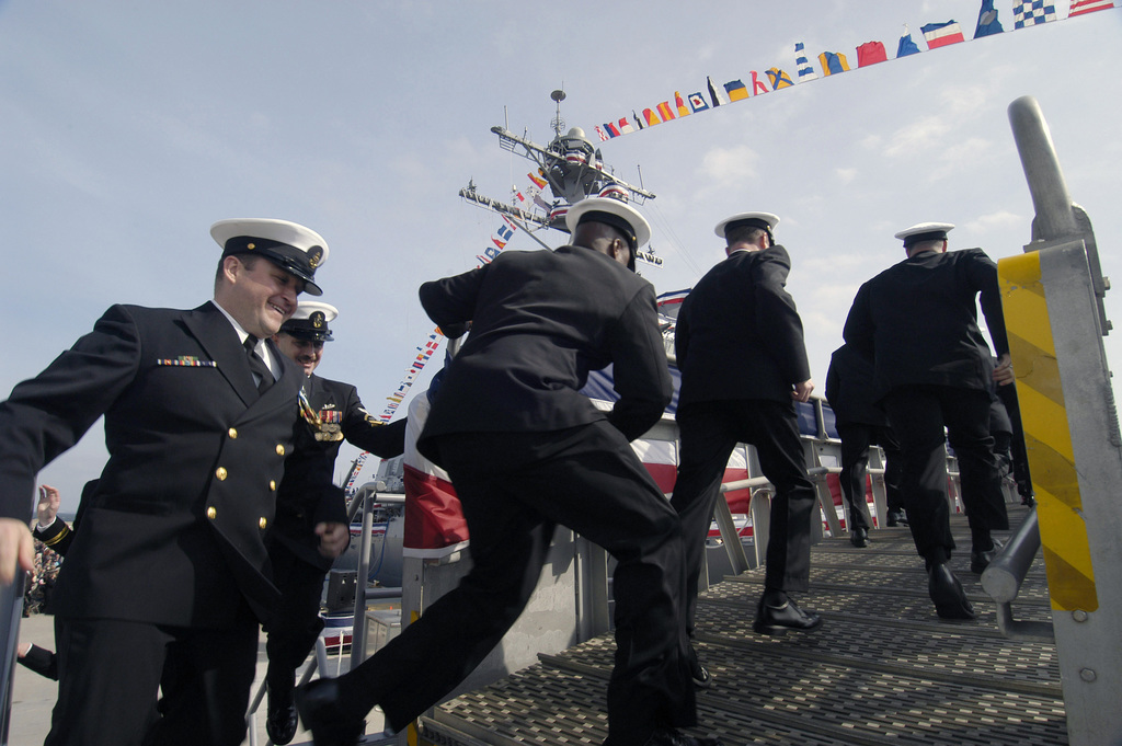 US Navy (USN) Sailors assigned aboard the Arleigh Burke Class (Flight IIA) Guided Missile Destroyer (Aegis) USS FORREST SHERMAN (DDG 98), man the ship, officially bringing it to life, during the Commissioning Ceremony at Naval Air Station (NAS) Pensacola, Florida (FL)