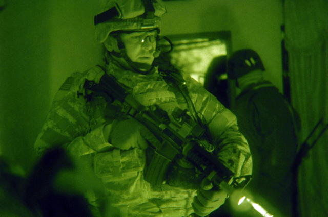 STAFF SGT. Robert Rittenhouse from B Battery, 4th Battalion, 320th Field Artillery Regiment, 4th Brigade Combat Team, 101st Division guards an Iraqi detainee during a target raid operation in Zafaraniyah district, Baghdad in the early morning of January 31, 2006.   The raid operation was conducted in search for a confirmed insurgent.(U.S. Army photo by SPECIALIST Teddy Wade) (Released)