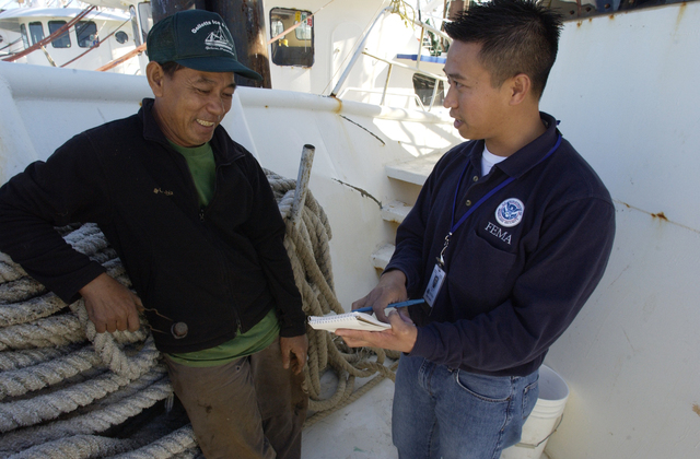 [Hurricane Katrina] Biloxi, MS, February 6, 2006 --Le, Phat a Vietnamese Fisherman on his 85' shrimp boat speaks with a FEMA representative. FEMA employs translators to assist victims through the assistance process. Community Relations staff member and translator Dylan VU tries to make sure all eligible applicants are aware of FEMA programs. Leif Skoogfors/FEMA Photo