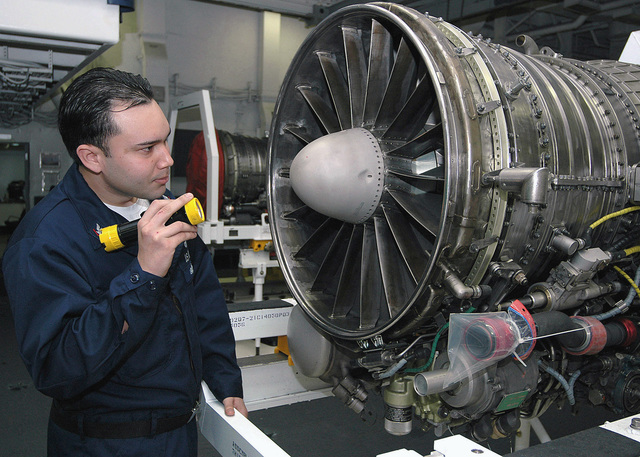 US Navy (USN) Aviation Machinists Mate Third Class (AD3) Moreao Salinas inspects a jet engine for any foreign object debris (FOD) inside the Aviation Intermediate Maintenance Department (AIMD) onboard the Nimitz Class Aircraft Carrier, USS GEROGE WASHINGTON (CVN 73)