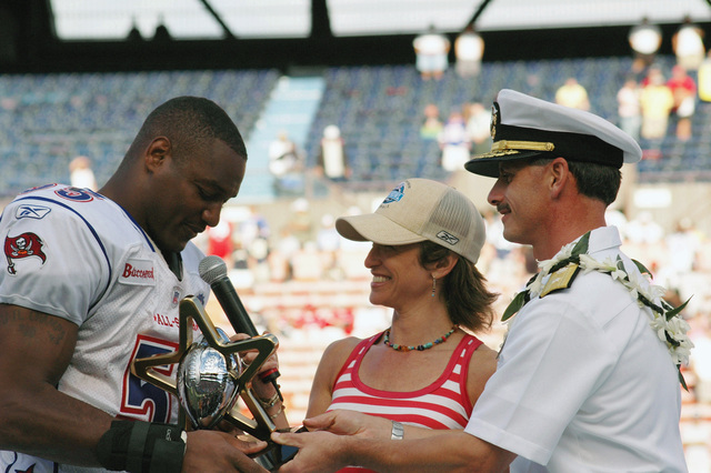 US Navy (USN) Rear Admiral (RDML) Michael C. Vitale (right), Commander, Navy Region Hawaii; and Commander, Naval Surface Group, Middle Pacific; presents the 2006 Pro Bowl Most Valuable Player (MVP) Award to Derrick Brooks )left), linebacker with the Tampa Bay Buccaneers, who is playing in his eighth National Football League (NFL) Pro Bowl