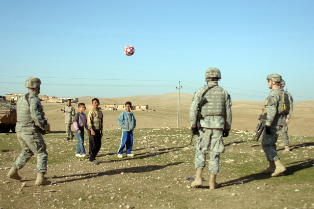 Soldiers of the 1ST Battalion,17th Infantry Regiment,172nd Stryker Brigade play soccer with Iraqi kids on 11 February 2006 in Mosul,Iraq in Support of Operation Iraqi Freedom.(U.S Army photo by SPC. Clydell Kinchen) (Released)