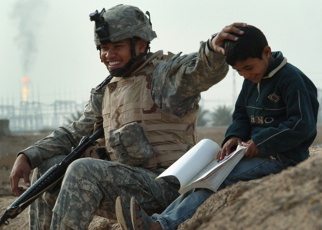 US Army (USA) SPECIALIST (SPC) Derek Castro, assigned to the 1-66th Battalion, 1ST Brigade, 4th Infantry Division, talks and jokes with Ali, a 10-year-old Iraqi boy, during a goodwill visit to the town of Istaqal, Iraq, during Operation IRAQI FREEDOM