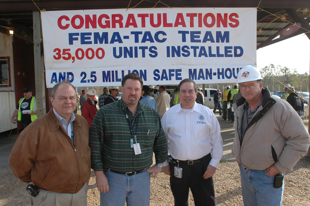 [Hurricane Katrina] Harrison County, Miss., February 14, 2006 -- Bob Weber, FEMA (left to right), Steven Overton, Bechtel, FEMA Deputy Federal Coordinating Officer (DFCO) Jesse Munoz and Troy Whiddon, Bechtel celebrate the installation of 35,000 travel trailers in Mississippi.  FEMA provides travel trailers as one form of temporary housing for residents affected by Hurricane Katrina.  Mark Wolfe/FEMA