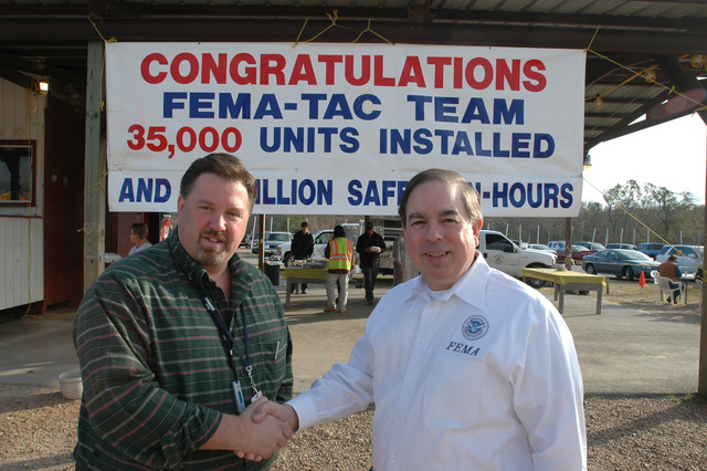 [Hurricane Katrina] Harrison County, Miss., February 14, 2006 -- FEMA Deputy Federal Coordinating Officer (DFCO) Jesse Munoz (right) thanks Steven Overton of Bechtel at a event celebrating the installation of 35,000 travel trailers in Mississippi.  FEMA provides travel trailers as one form of temporary housing for residents affected by Hurricane Katrina.  Mark Wolfe/FEMA